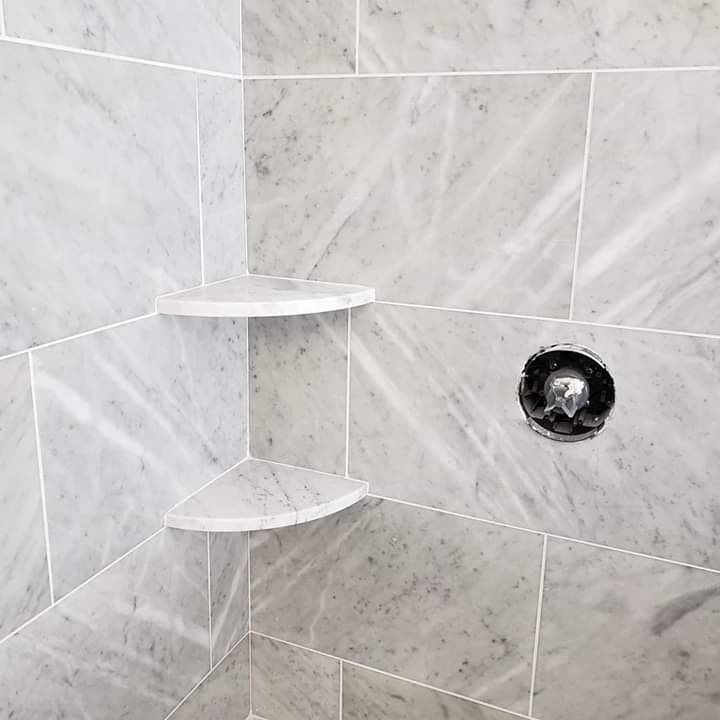 marble shower with corner shelves