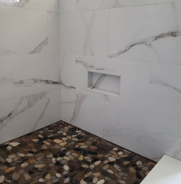 porcelain shower with pebble floor and soap niche